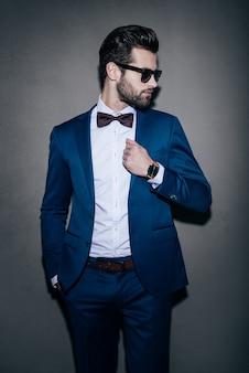 彼のスタイルにぴったりです。サングラスをかけてジャケットを調整し、灰色の背景に立っている間彼の肩越しに見ているハンサムな若い男