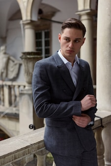 Perfect to the last detail. handsome young businessman adjusting his sleeves while standing against grey wall