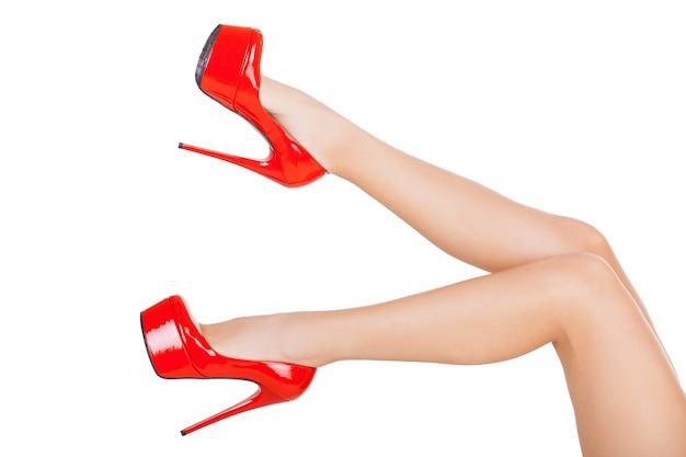 完璧な脚。白で隔離の赤いハイヒールの靴で美しい女性の脚のクローズアップ