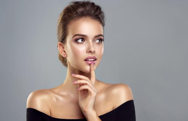 Идеально выглядящая модель в элегантном макияже с розовой помадой смотрит в сторону с любопытством эмоции