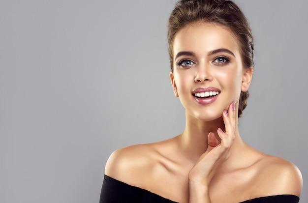 Идеально выглядящая модель в элегантном макияже смотрит на зрителя с зубастой улыбкой и касается лица