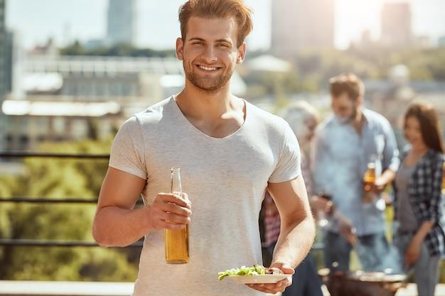 若くてハンサムな男がビールとプレートのボトルを持っている友人との完璧なランチ