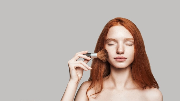 Perfect make up. portrait of attractive and young woman with long red hair applying make-up and keeping eyes closed while standing against grey background. make up concept