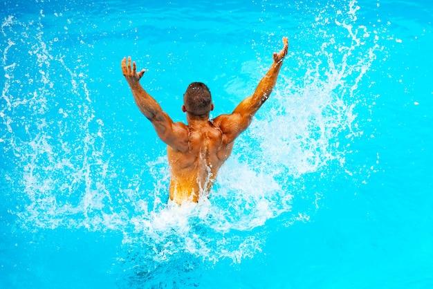 Идеальный мужской торс на фоне голубой воды. отдых в раю. отпуск. эксперт по роскошным путешествиям