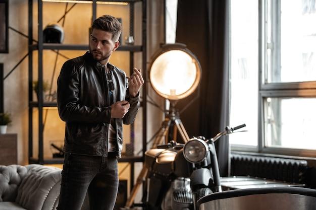 完璧な男。部屋に立っている革のジャケットの若いヒップスター。