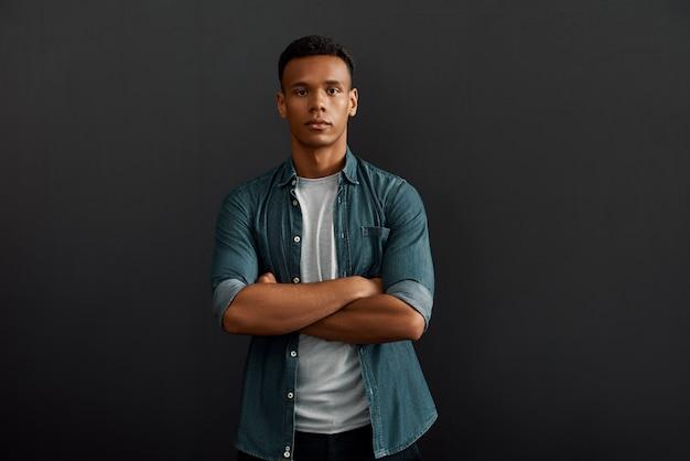 カメラを見て腕を組んでいる完璧なマネージャーハンサムで若いアフリカ系アメリカ人の男