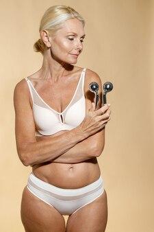 Идеальная зрелая блондинка в нижнем белье со светящейся кожей держит металлический ролик для лица, улыбаясь в сторону
