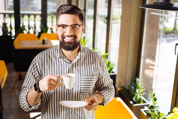 Прекрасное настроение. веселый счастливый человек улыбается вам, стоя с чашкой кофе