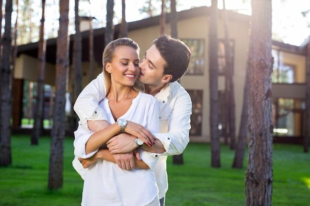 完璧な気分。彼の気持ちを表現しながら彼の最愛の妻にキスする喜んでうれしそうな男