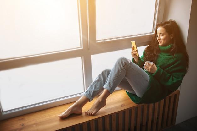 完璧な朝若いブルネットの女性は窓辺に座って、スマートフォンを持っています。