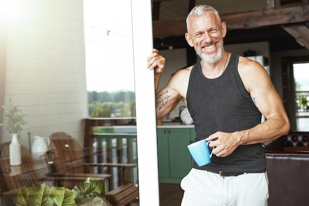 テラスの近くに立っているコーヒーと完璧な朝ハンサムなポジティブ中年白人男性