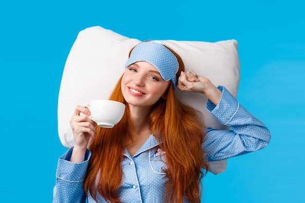 Perfect morning of princess. cheerful, tender redhead woman with long ginger hair, wearing sleep mask and pyjama, stretching in bed feeling fresh and energized, drink morning coffee, blue wall