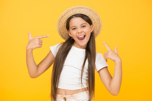 완벽한 복장. 밀 짚 비치 모자에 행복 한 아이입니다. 여름 휴가 및 휴가. 좋은 분위기와 여가 시간. 아이 패션과 뷰티. 행복한 어린 시절. 수확 및 농업 개념입니다. 따뜻한 봄날.