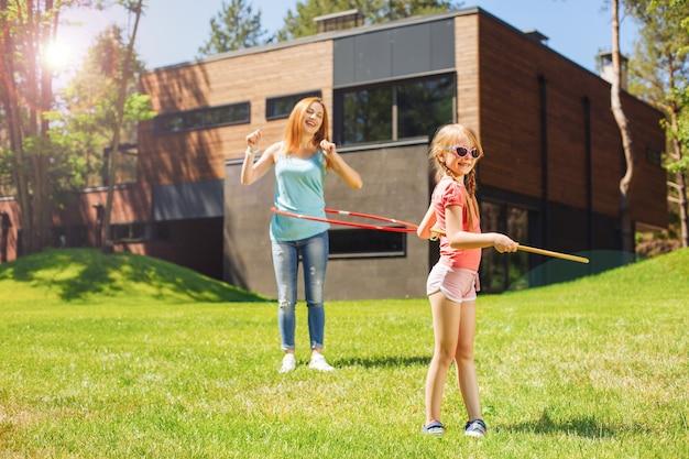 Прекрасное времяпрепровождение. жизнерадостная молодая мама и ее маленькая дочь делают утреннюю зарядку в парке и играют со своими обручами.