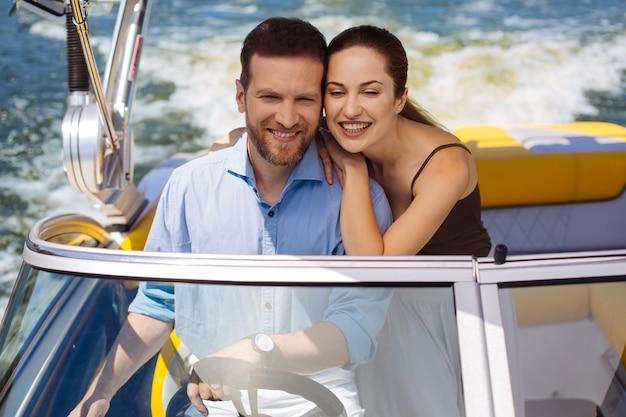 完璧な購入。新しいヨットで乙女の航海をし、幸せそうに笑っている幸せな若いカップル