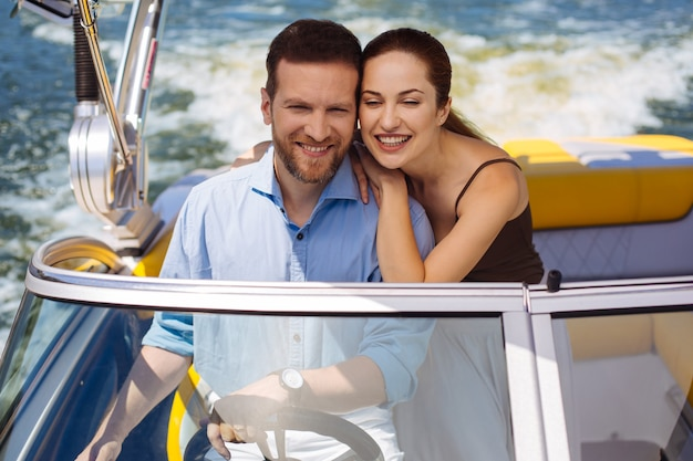 Perfect purchase. happy young couple having a maiden voyage on their new yacht and smiling happily