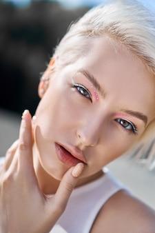 Идеальный красный маникюр на ногтях блондинки с короткими волосами. женщина позирует летом на природе в солнечный день
