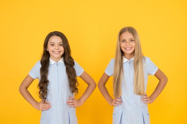 완벽한 여학생들. 여학생 빈티지 심플한 스타일의 의상. 쾌활 한 여 학생 노란색 배경입니다. 어린 소녀들. 행복한 어린이날. 동등한 보호 시민권과 차별로부터의 자유.