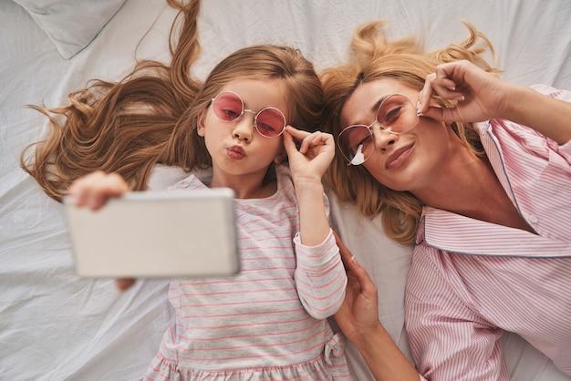 完璧な自撮り。若い美しい母親と彼女のかわいい娘がスマートフォンでselfieを取り、自宅のベッドに横たわっている間笑顔の上面図
