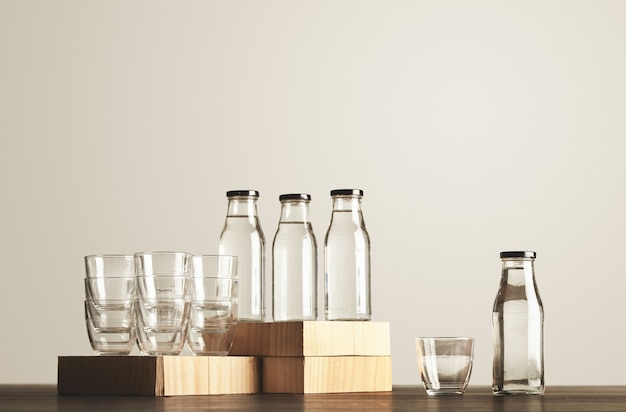 Perfect set of pure clean healthy water in transparent glass bottles and cups presented on wooden