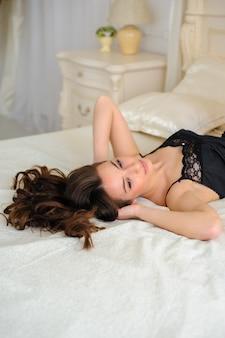 完璧な肌を持つ完璧なセクシーな日焼け女性、寝室でポーズをとって大きな完全な唇、セクシーで豪華なスタイリッシュな黒のランジェリーを着ています。