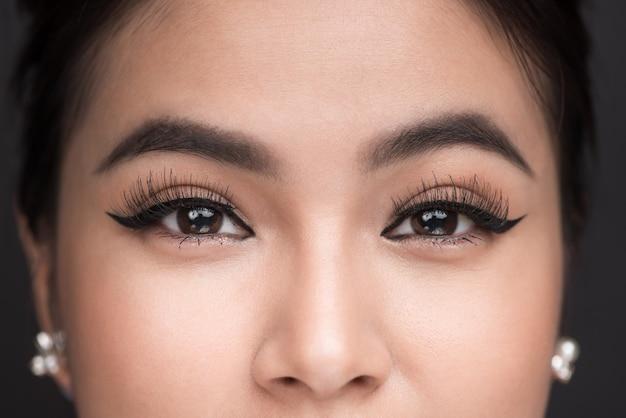眉毛の完璧な形。古典的なアイライナーメイクで女性の目の美しいマクロ撮影。