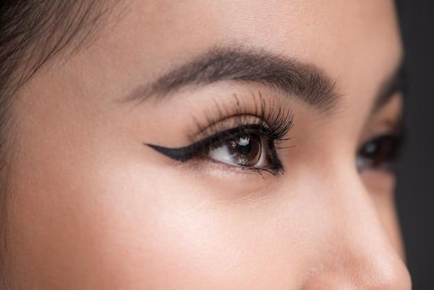 완벽한 눈썹 모양. 클래식 아이라이너 메이크업으로 여성 눈의 아름다운 매크로 샷.