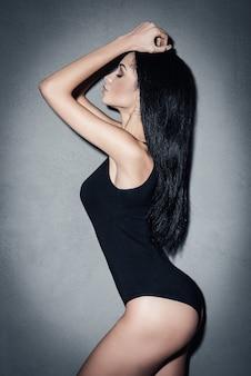 完璧な形。灰色の背景に立っている間ポーズをとって目を閉じたまま黒い水着で美しい若いアフリカの女性の側面図
