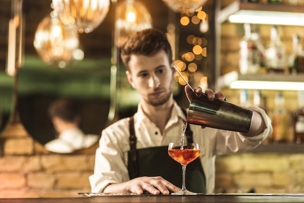 Perfect skills. pleasant young barman standing behind a bar counter, mixing a cocktail and pouring the beverage into the glass