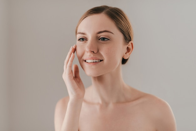 Идеальная кожа. студийный портрет привлекательной женщины с веснушками на лице, касающейся ее кожи и улыбающейся, стоя на фоне