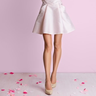 Perfect slim long female legs and pink dress