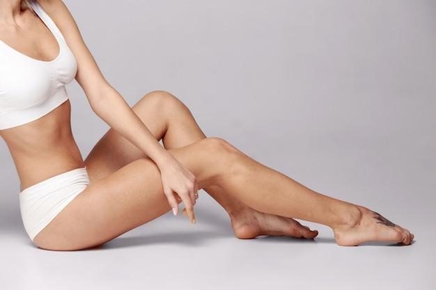 スタジオで女の子やフィットの女性の完璧なスリムなトーンの若い体。フィットネス、ダイエット、スポーツ、形成外科、美容美容のコンセプト。画像は体型レタッチされていません