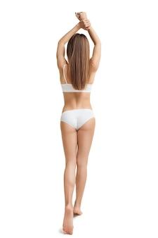 スタジオで女の子やフィットの女性の完璧なスリムなトーンの若い体。
