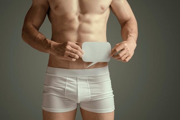 男性の完璧なスリムなトーンの若い体、または灰色の背景のスタジオで筋肉モデルにフィットします。ふきだしを持っています。スポーツ、ダイエット、健康的なライフスタイル、ボディービル、フィットネス、ヘルスケアの概念。