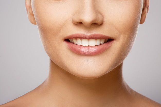 Perfect smile at gray studio background, a model with light nude make-up, perfect teeth, shining smile, close up.
