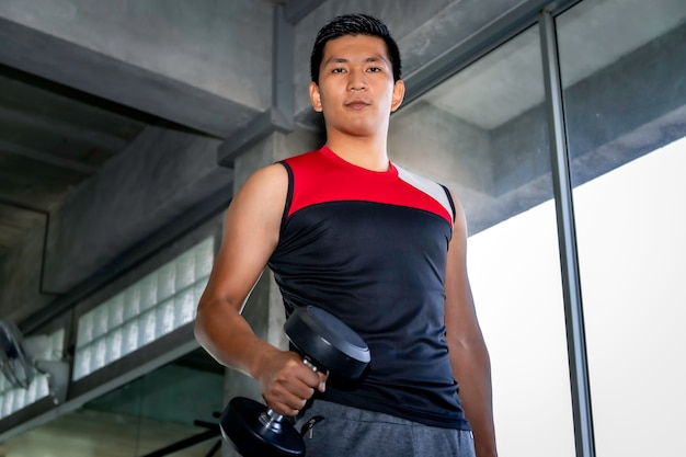 Perfect strong bodybuilder athletic asian man workout arm with dumbbell on gym.