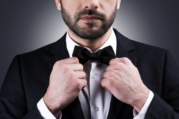 完璧なスタイル。灰色の背景に立っている間彼の蝶ネクタイを調整する正装でハンサムな成熟した男のクローズアップ