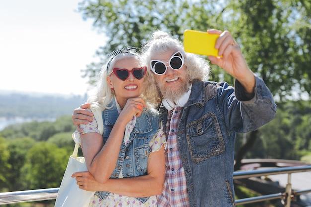 完璧なスタイル。一緒に写真を撮りながらサングラスをかけて喜んでいるお年寄り