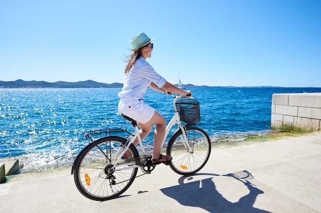 Идеальный летний пейзаж. довольно улыбающийся стройная туристическая женщина езда на велосипеде на берегу моря на ярко сверкающей воде, чистое голубое небо, парусный корабль и горы