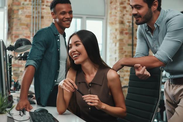 젊고 쾌활한 세 사람의 완벽한 팀워크 그룹은 새로운 아이디어를 논의하고 웃는 동안