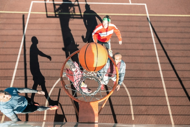 完璧なスロー。バスケットボールの試合中にバスケットに落ちるオレンジ色のボールの上面図