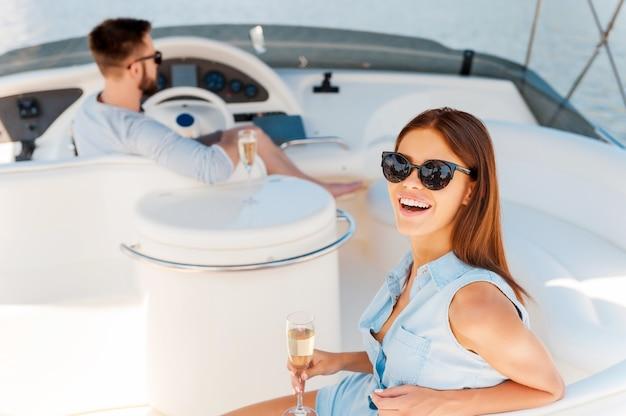 一緒に完璧な時間。彼女のボーイフレンドがヨットを運転している間、シャンパンでガラスを保持し、カメラを見ている美しい若い女性