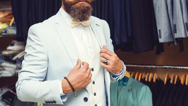 細部まで完璧です。現代のビジネスマン。エレガントなクラシックなスーツを着たハンサムな男のファッションショット。男性の美しさ、ファッション。明るい青色のスーツでハンサムな残忍なひげを生やしたヒップスターの男