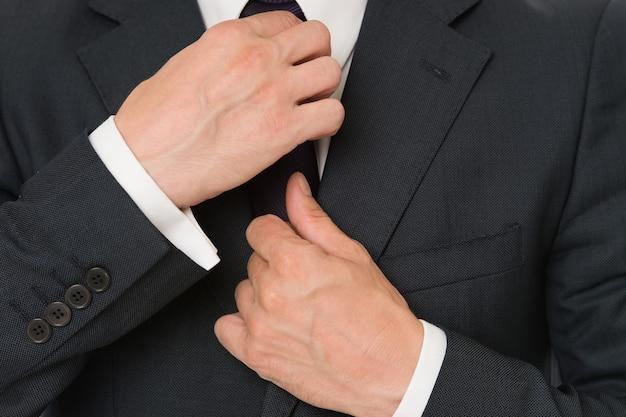 細部まで完璧です。スタイリッシュなディテールのビジネスルック。ビジネススタイルのドレスコード。ネクタイビジネススタイルの衣装を固定する男性の手。彼のスタイルに自信を持っています。ビジネスマンはフォーマルな服を選びます。