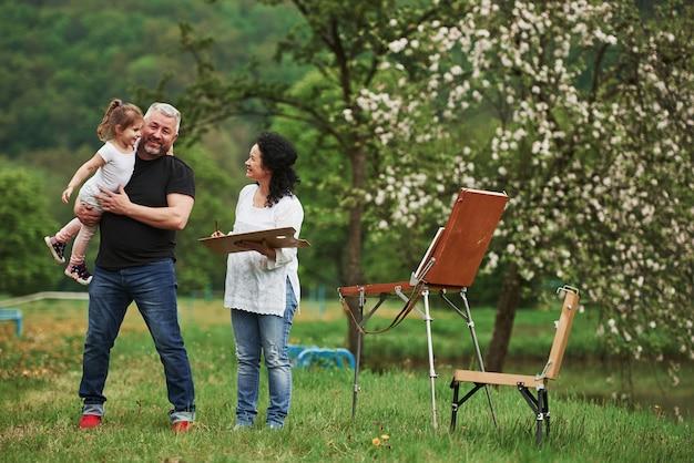 Прекрасная теплая погода. бабушка и дедушка веселятся на природе с внучкой. концепция живописи