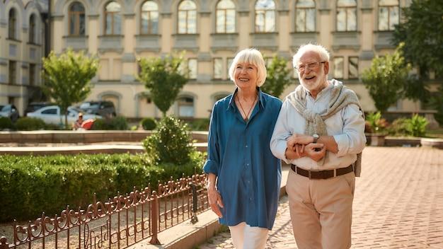 Прекрасная погода, счастливая и красивая пожилая пара, держась за руки во время прогулки на свежем воздухе