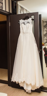 The perfect wedding dress on a hanger in the room of bride.