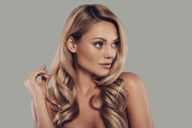 Идеальная женщина. привлекательная молодая женщина с длинными вьющимися светлыми волосами улыбается и смотрит в сторону, стоя на сером фоне