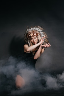 Perfect woman in garb of american indians in smoke