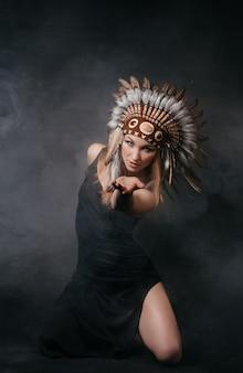 회색 배경에 연기가 나는 아메리칸 인디언 복장을 한 완벽한 여성. 깃털로 만든 모자. 신비로운 신비로운 길, 섹시한 몸매, 아름다운 등. 아름다운 얼굴을 가진 매력적인 금발